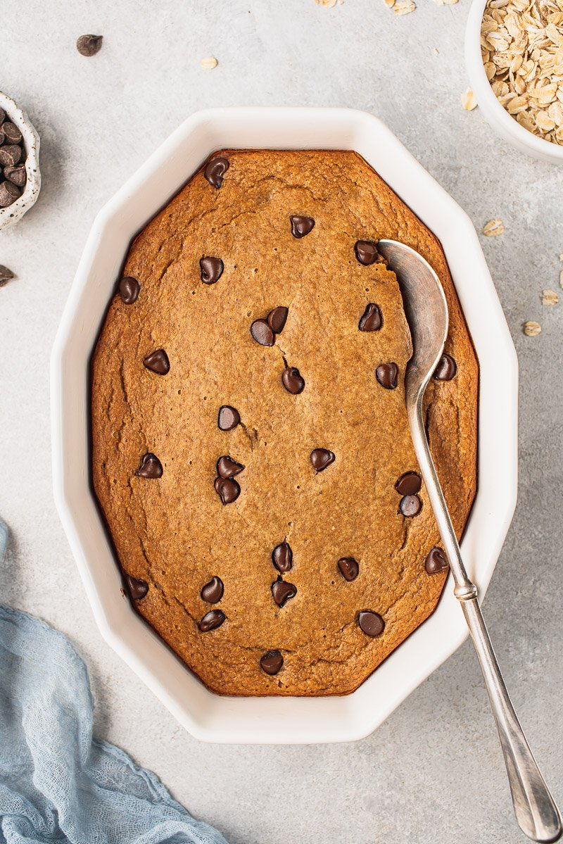 an overhead photo of chocolate chip baked oatmeal with a serving spoon
