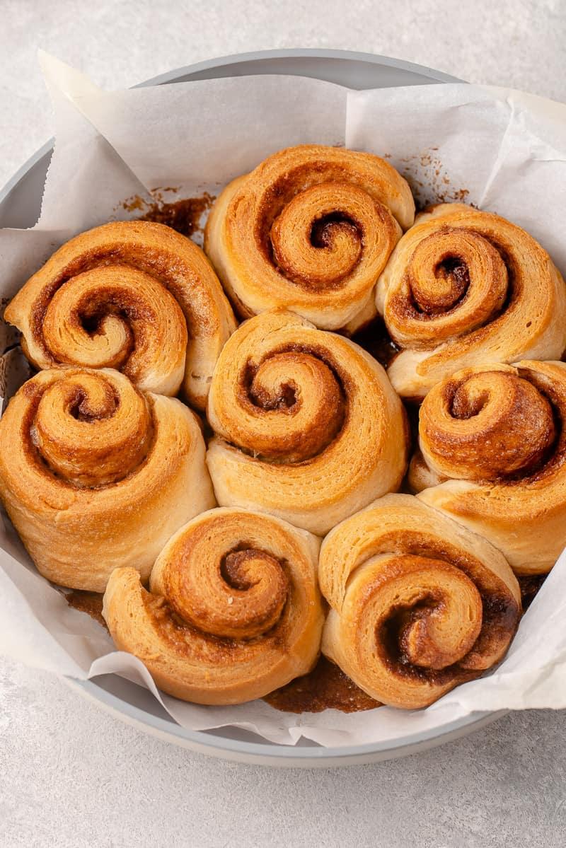 overhead image of cooked cinnamon rolls in pan