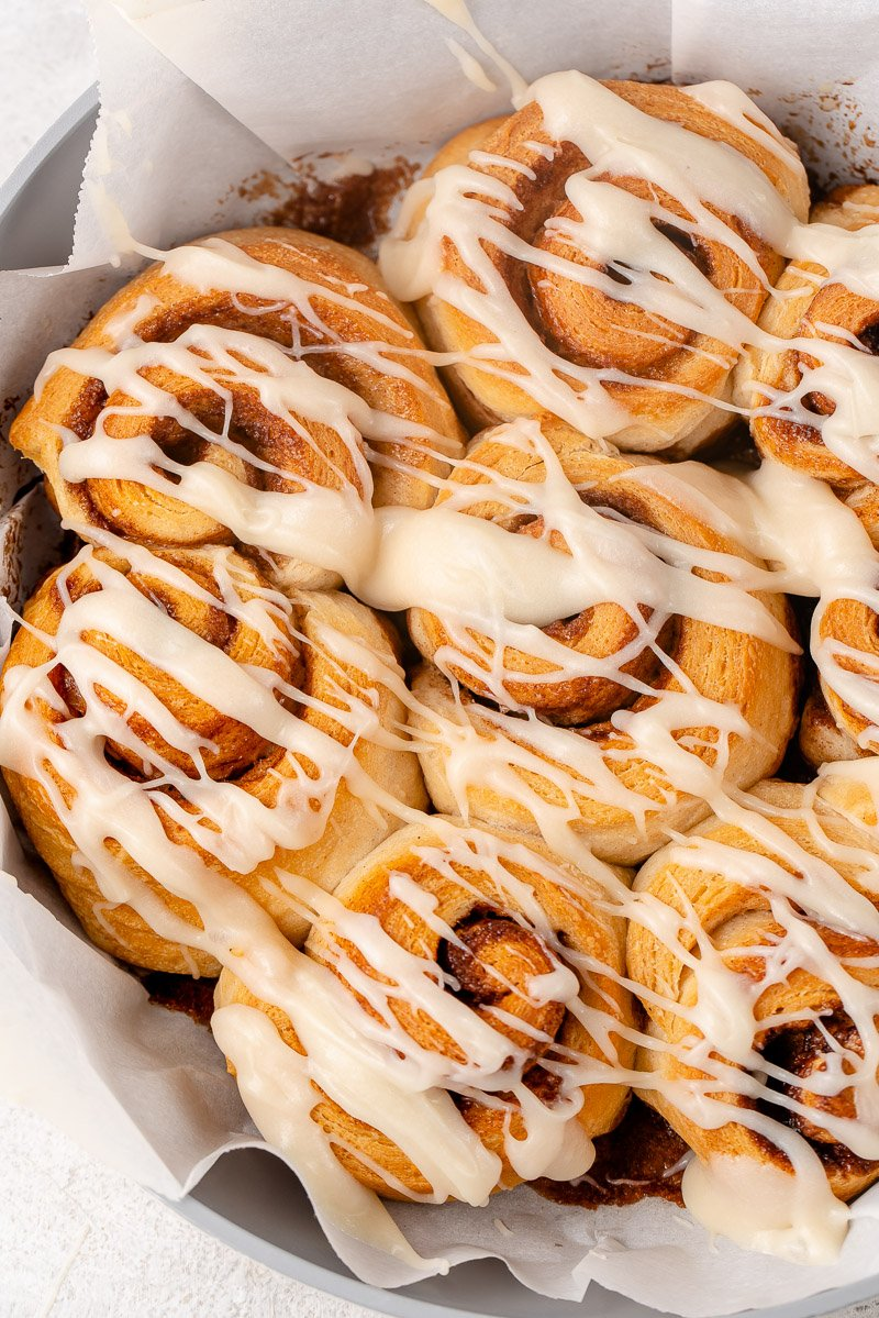 overhead image of cooked cinnamon rolls drizzled with icing