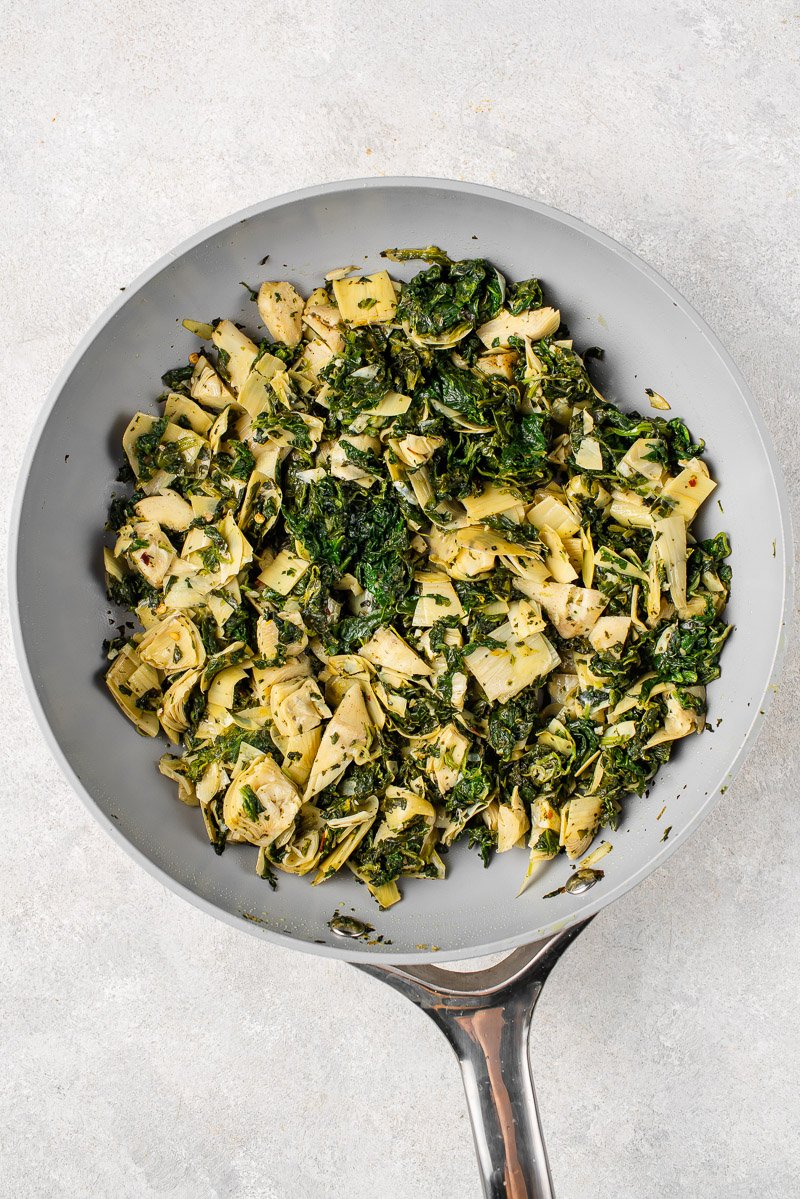 Overhead image of baked spinach artichoke mac and cheese in pan before sauce is added