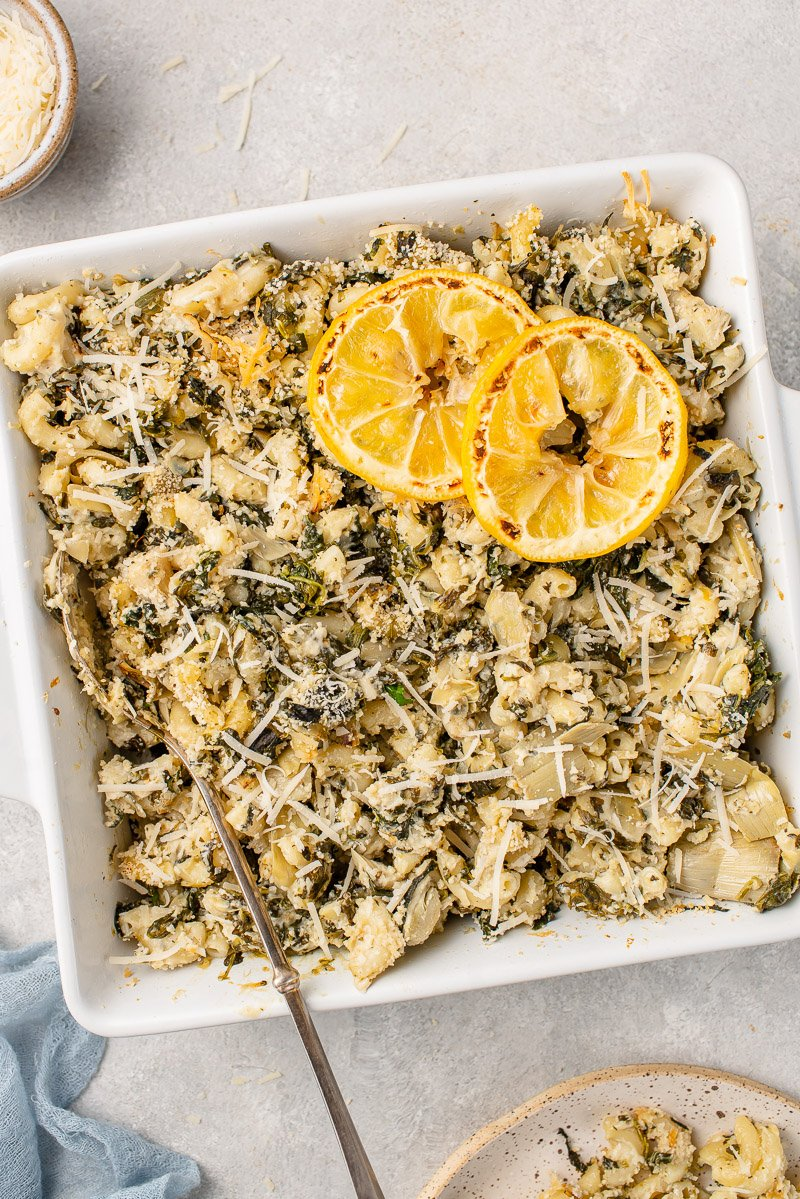 Overhead image of baked spinach artichoke mac and cheese in baking dish with spoon.