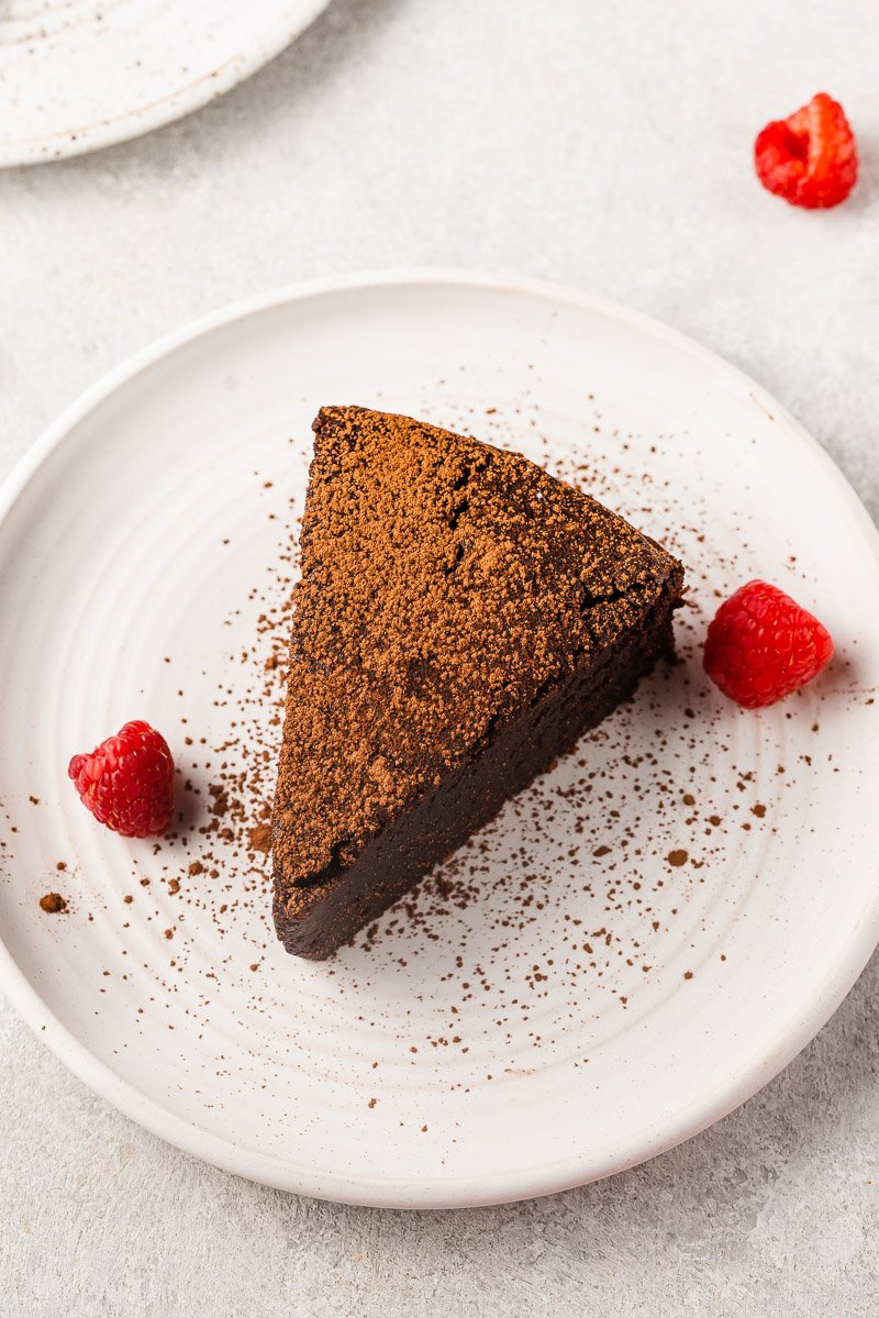 overhead image of chocolate soufflé cake dusted with cocoa powder up close with raspberries