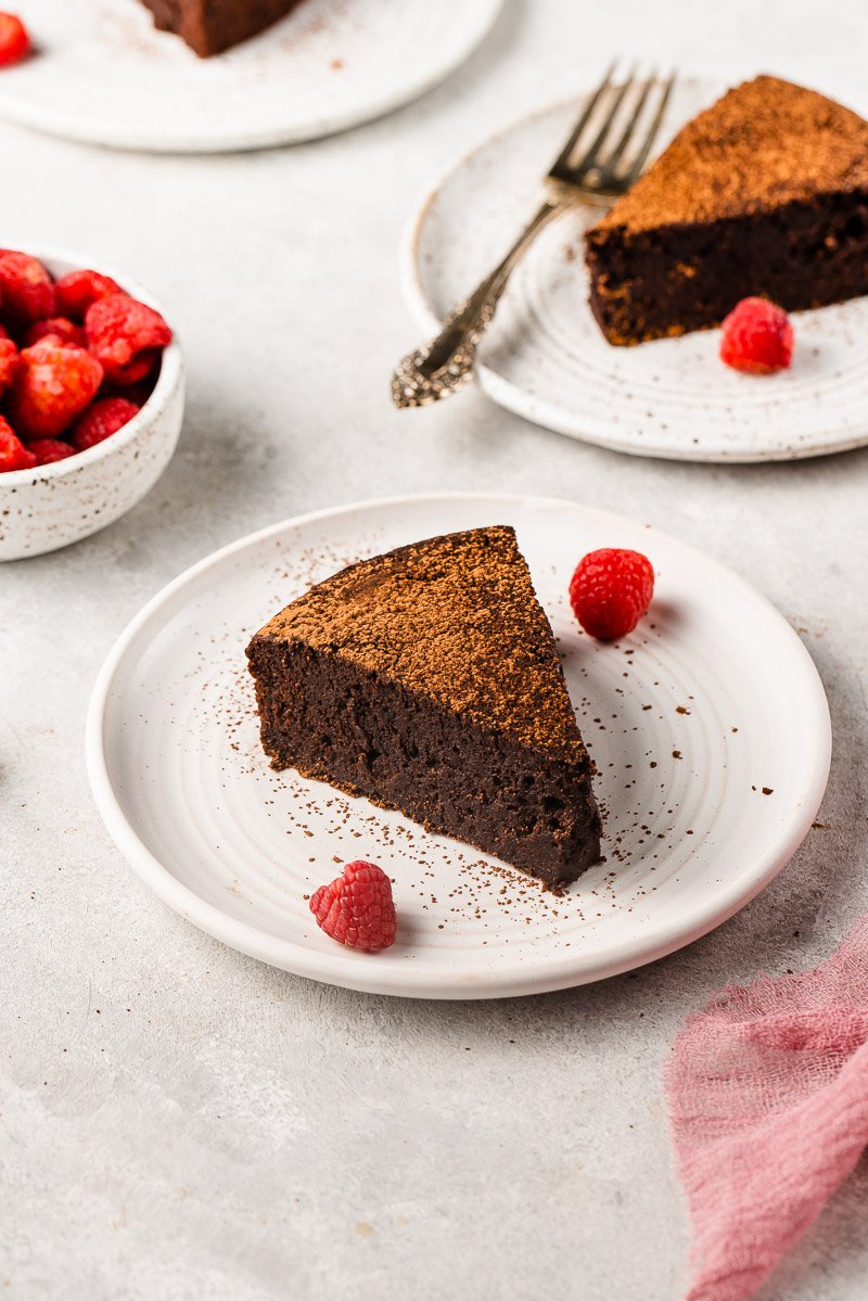 straight forward image of chocolate soufflé cake dusted with cocoa powder and raspberries
