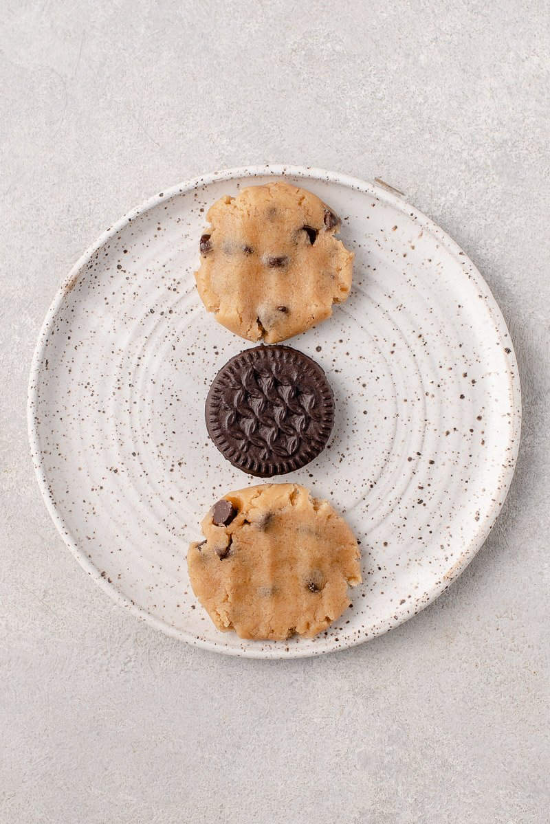 over head image of cookies being assembled. Two flat pieces of chocolate chip cookie dough on the outside and oreo cookies in the middle.