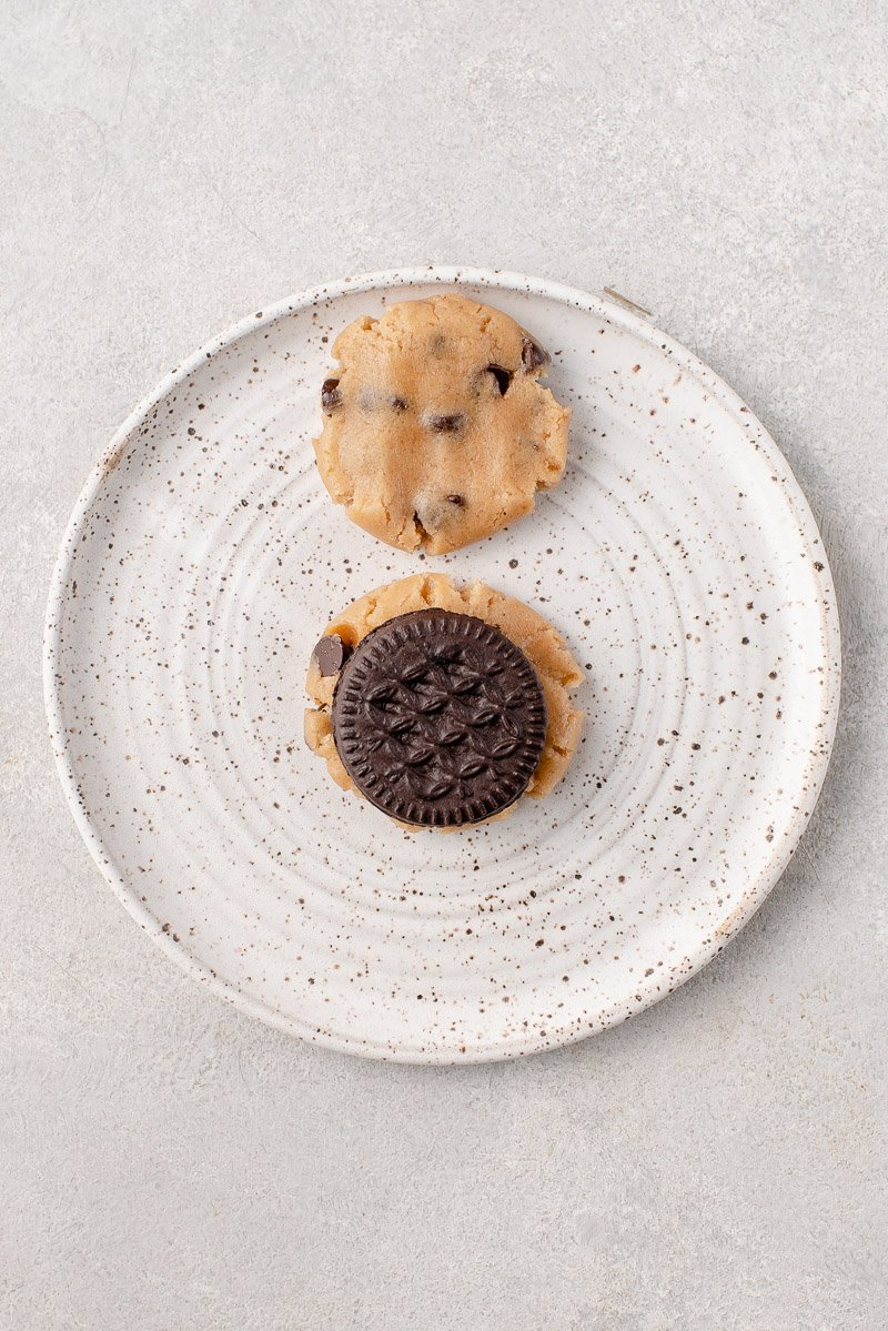 over head image of cookies being assembled. Two flat pieces of chocolate chip cookie dough with an oreo cookie on one of them. .