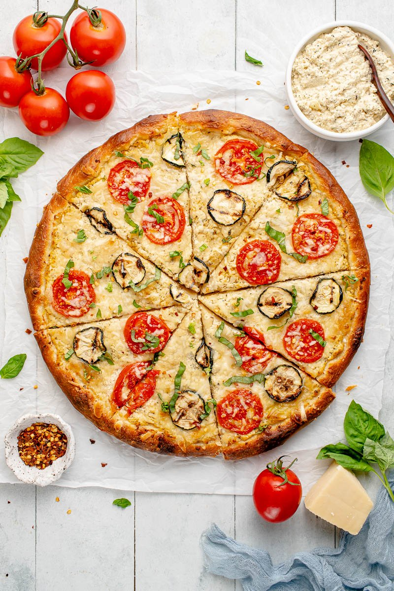 overhead image of white pizza with zucchini and tomatoes on styled background