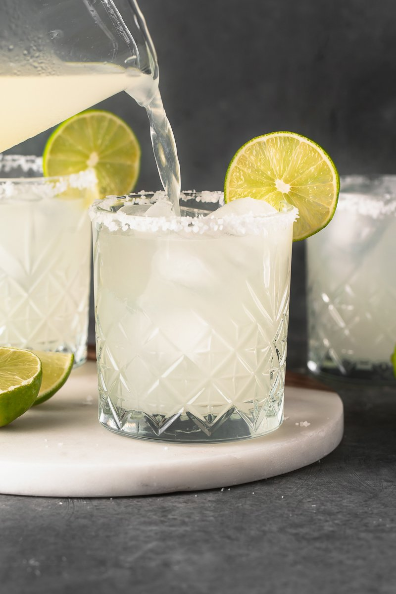 classic margarita being poured into a glass from the pitcher