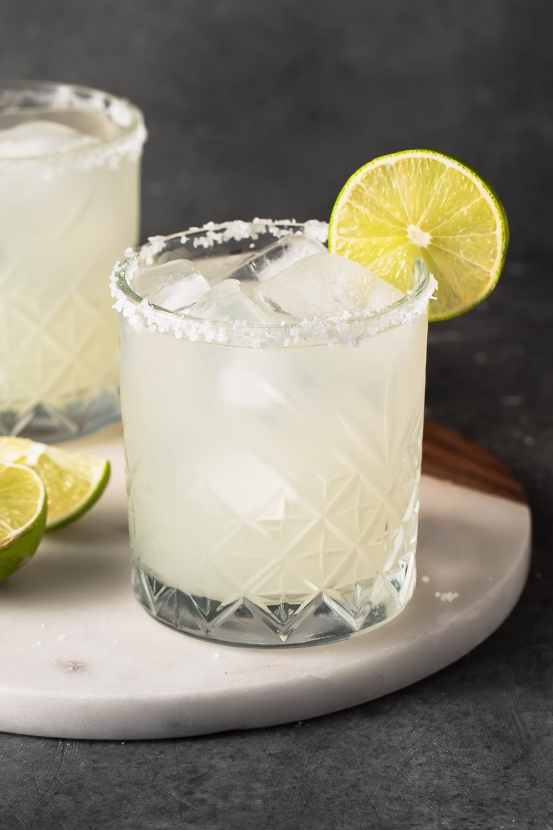 straight forward image of classic margarita in a glass with a lime garnish