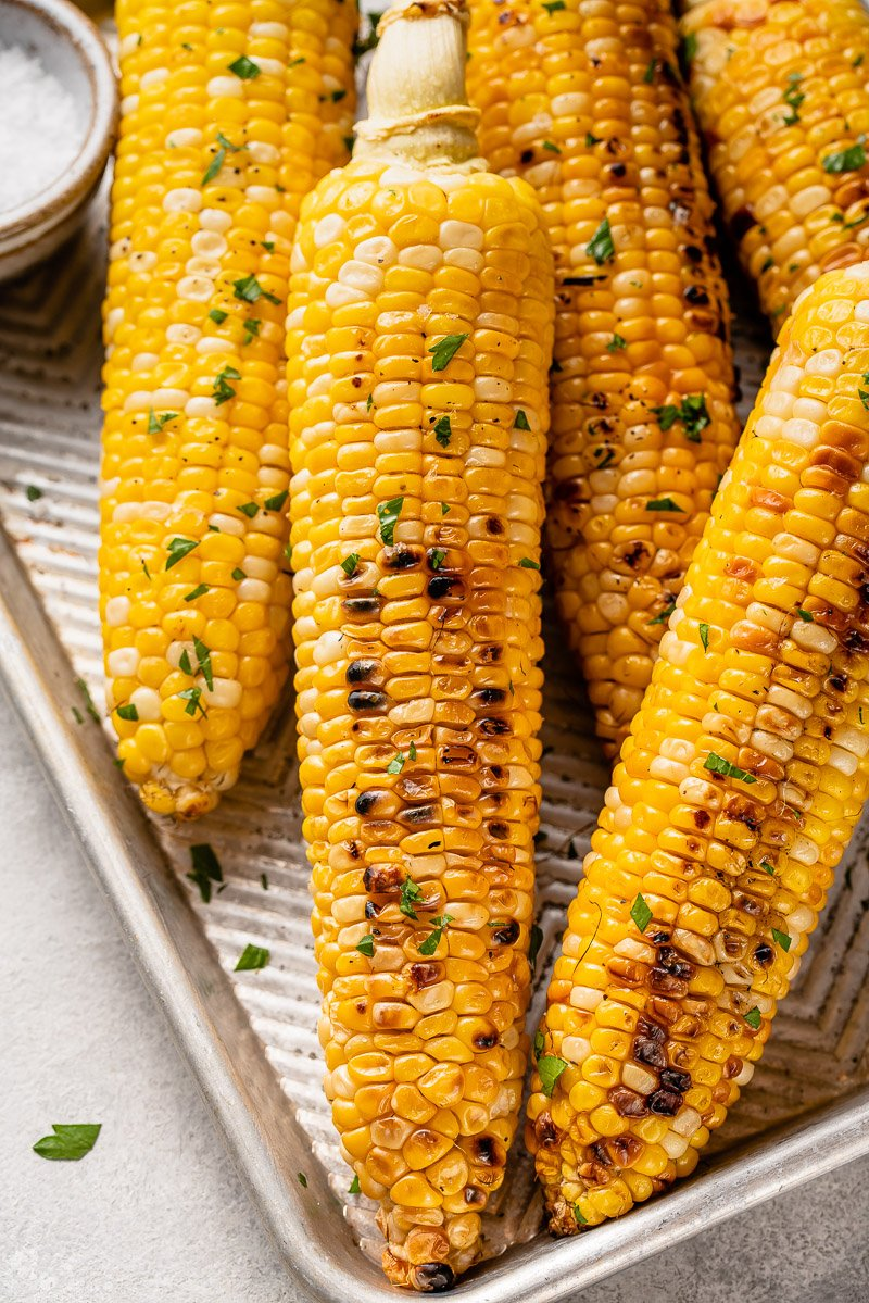 grilled corn on a baking sheet with butter and parsley