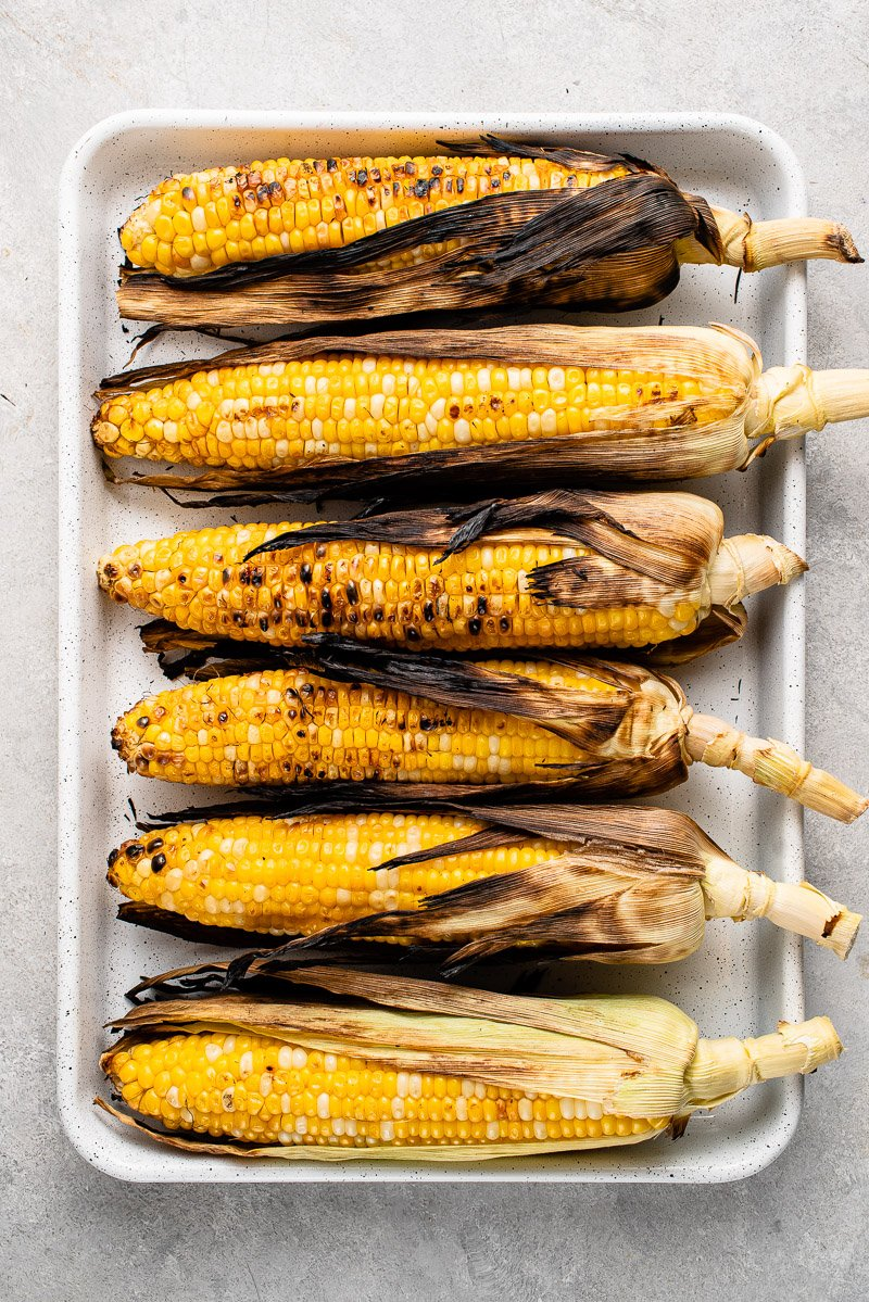 grilled corn on a white baking dish