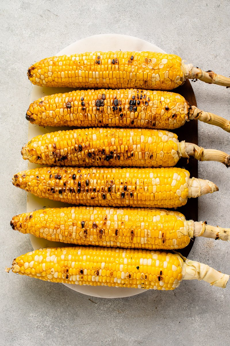grilled corn on a white serving platter