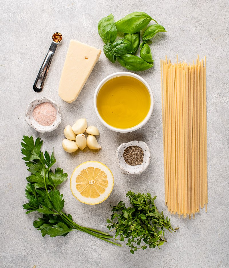 ingredients to make garlic and herb pasta on a gray board
