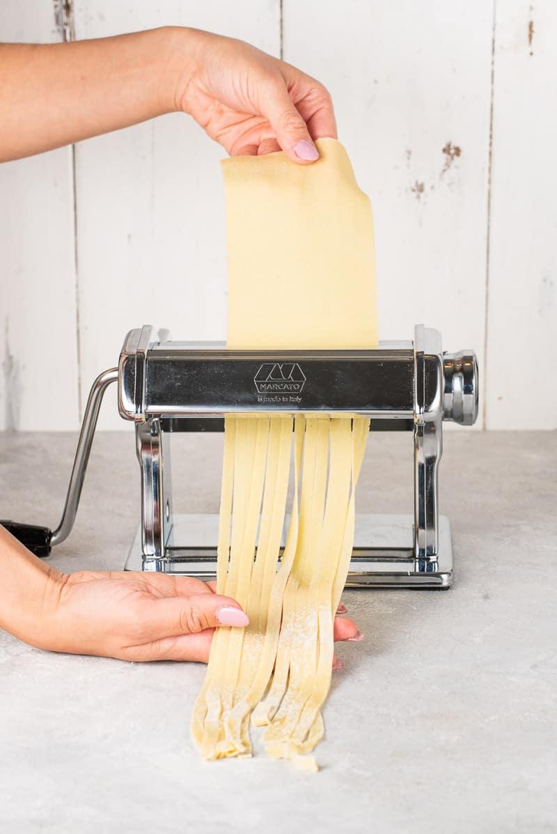 pasta being run through a pasta machine