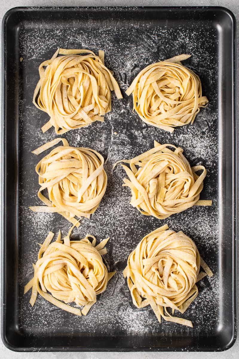 homemade vegan egg pasta nests on a metal pan