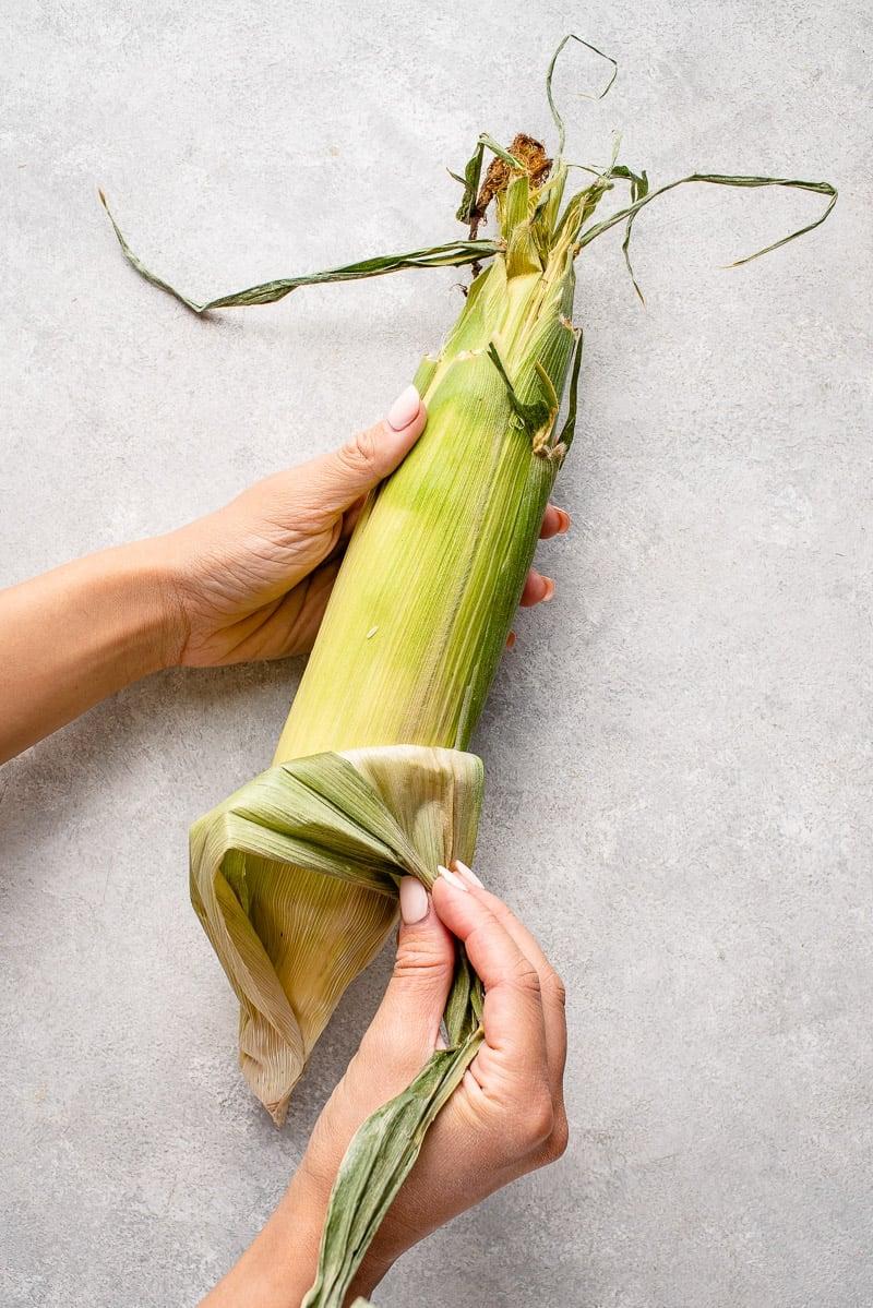peeling husk off of corn