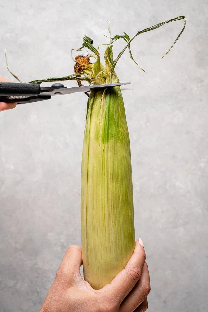 photo of scissors trimming the husk on corn