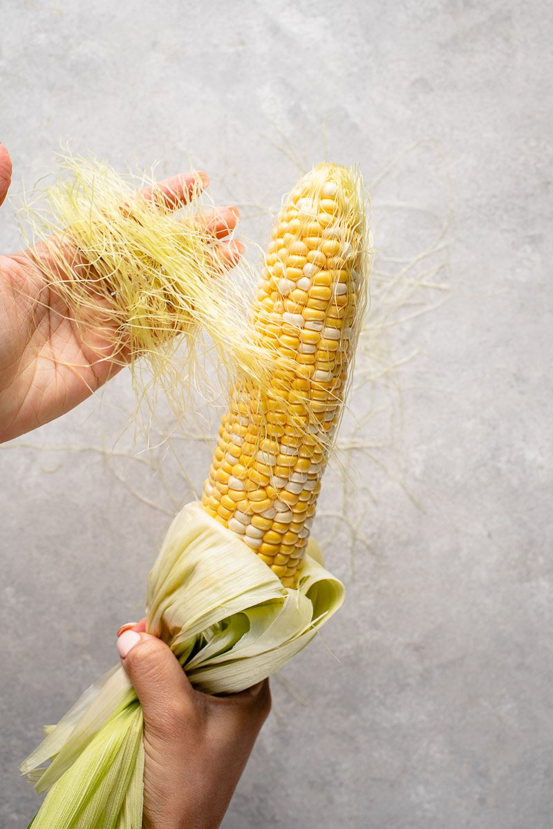 pulling the silks off corn