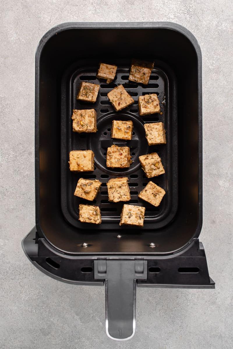 uncooked herbed tofu in air fryer basket.