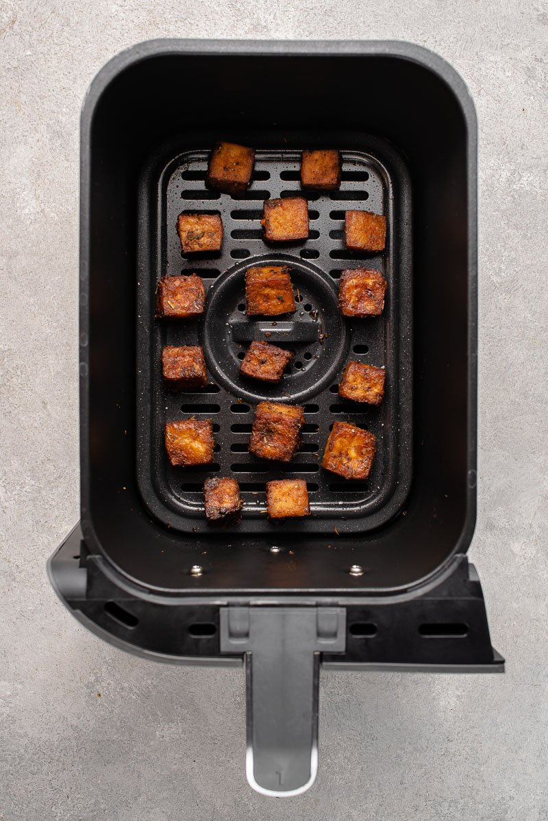 overhead image of cooked tofu in an air fryer basked