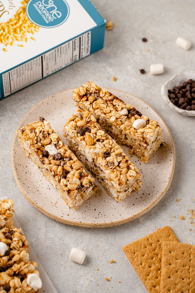 three quarter angled image of granola bars on plate with box in background