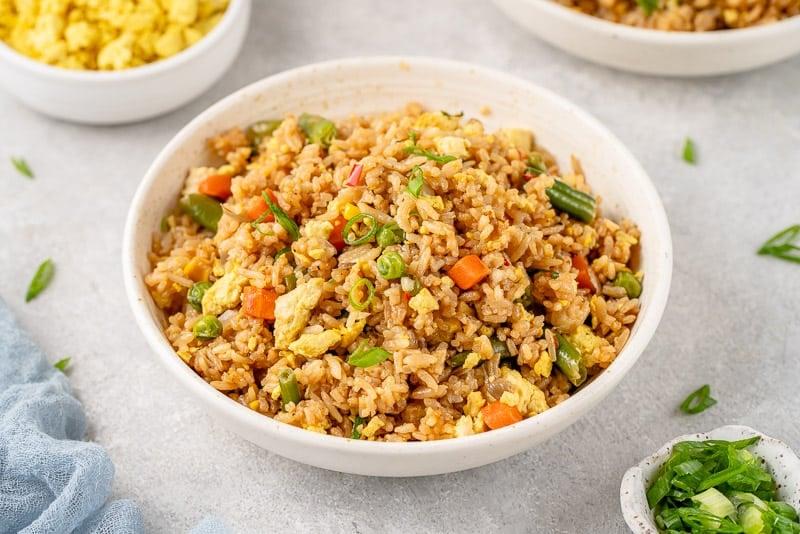 3/4 image of bowl of fried rice on styled grey background