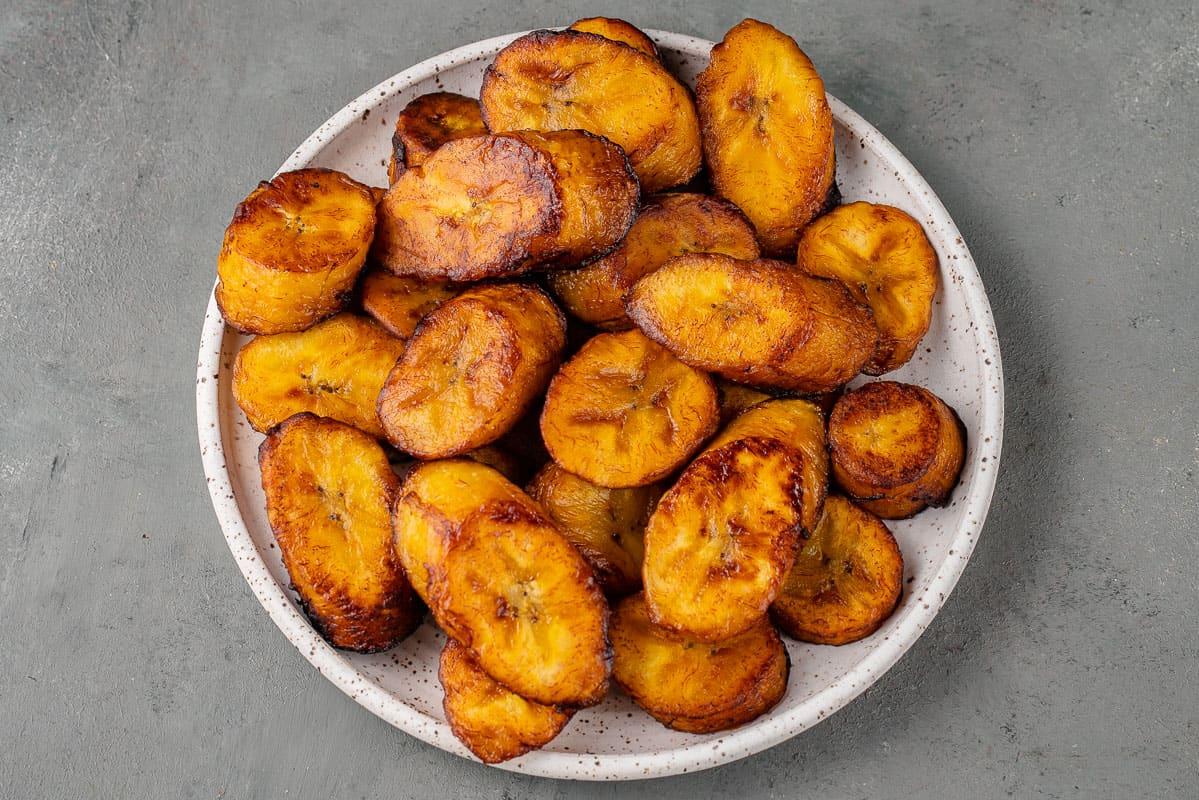 landscape image of Plátanos Maduros Fritos (Fried Ripe Plantains) on a plate