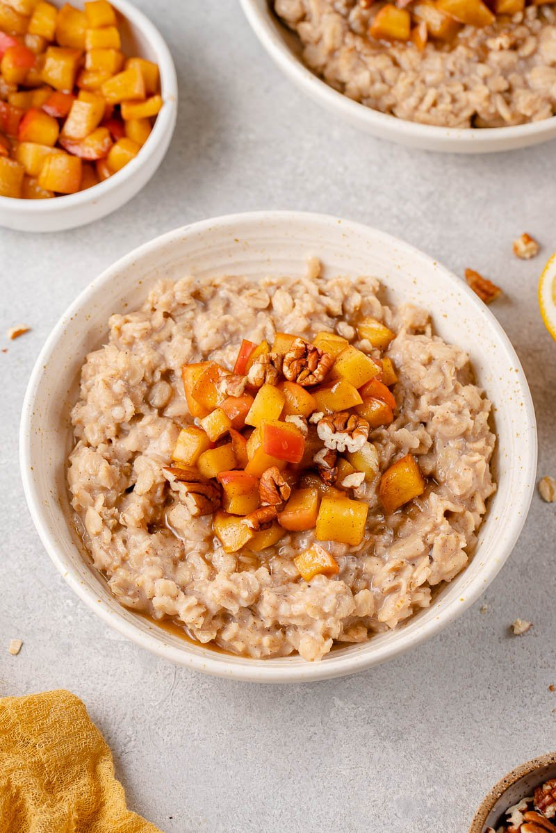 three quarter angle of apple cinnamon oatmeal in a bowl styled on a grey background