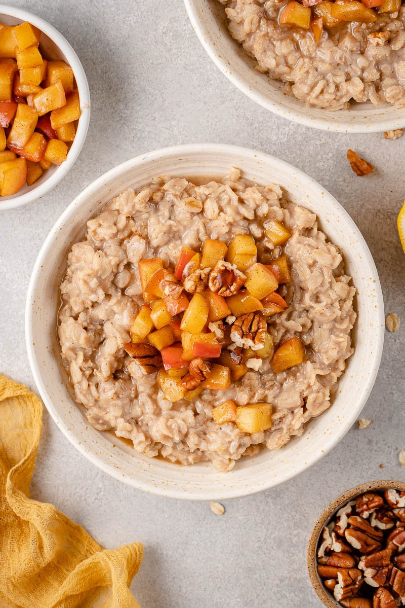 Overhead image of apple cinnamon oatmeal in bowl styled on a grey background