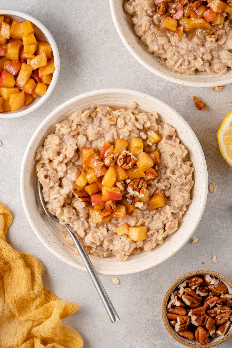 Overhead image of apple cinnamon oatmeal in bowl with a spoon styled on a grey background