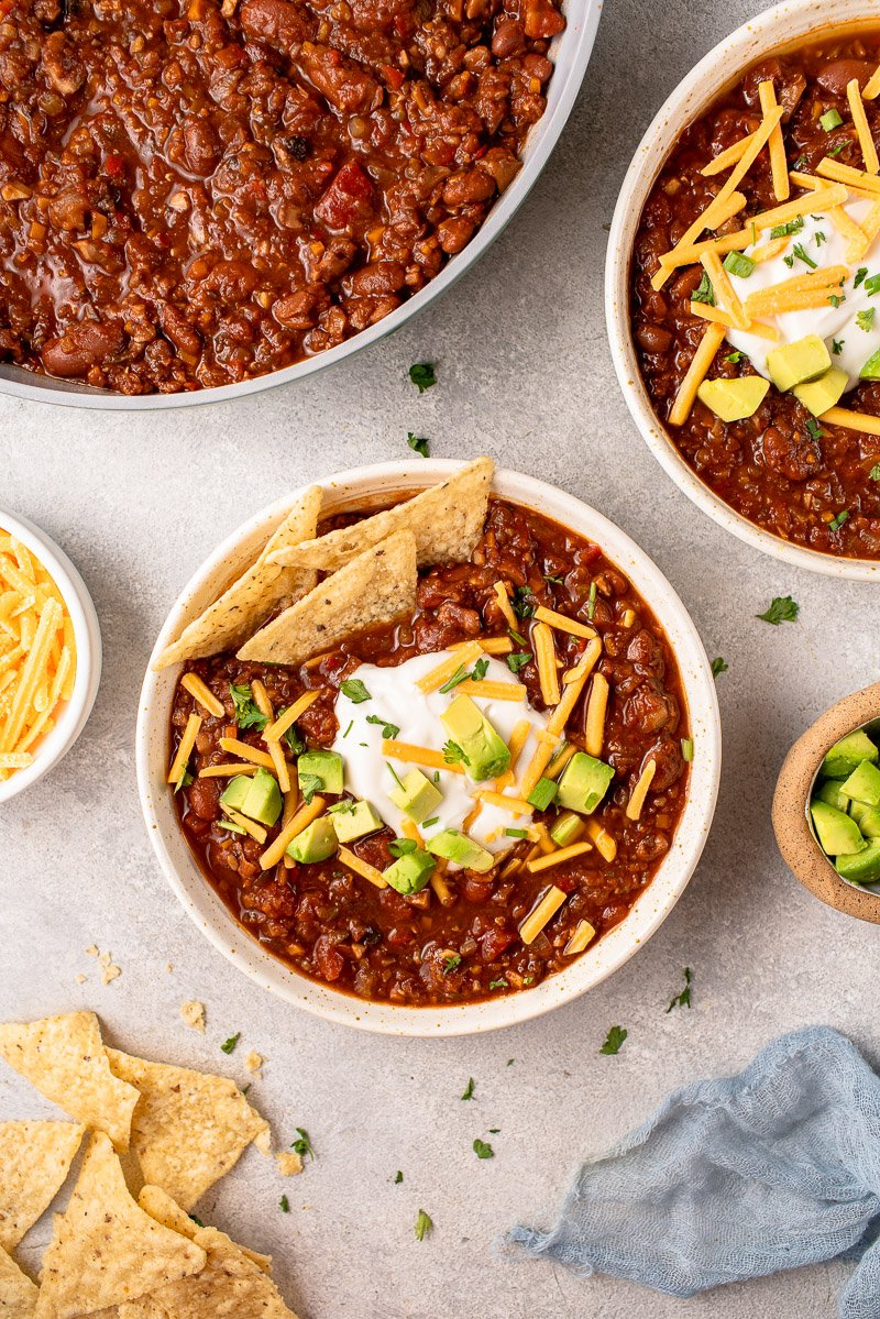 overhead image of bowls of chili styled with vegan cheese and chips