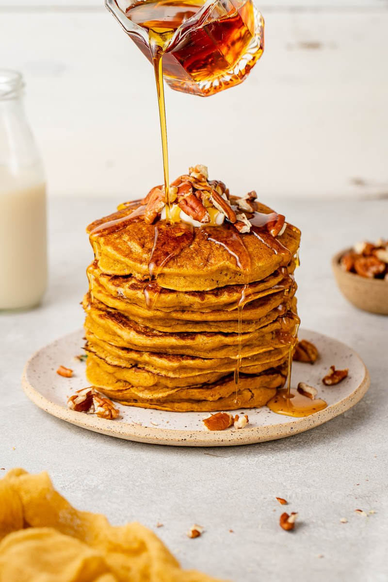 up close image of syrup being poured onto pumpkin pancakes