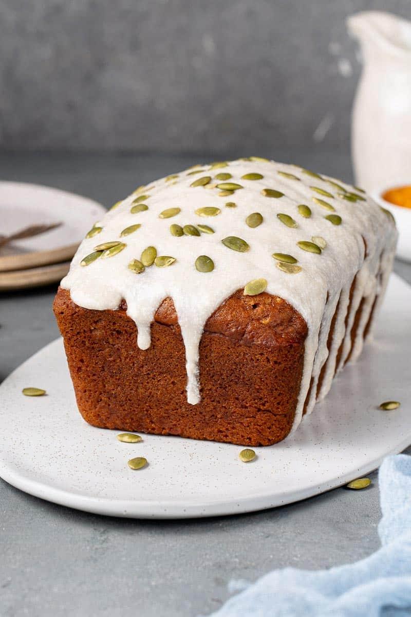 vegan pumpkin bread with cream cheese icing and pumpkin seeds