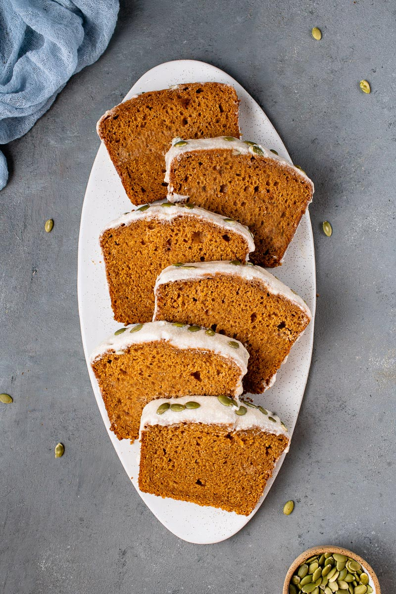 overhead photo of stacked slices of vegan pumpkin bread on white board