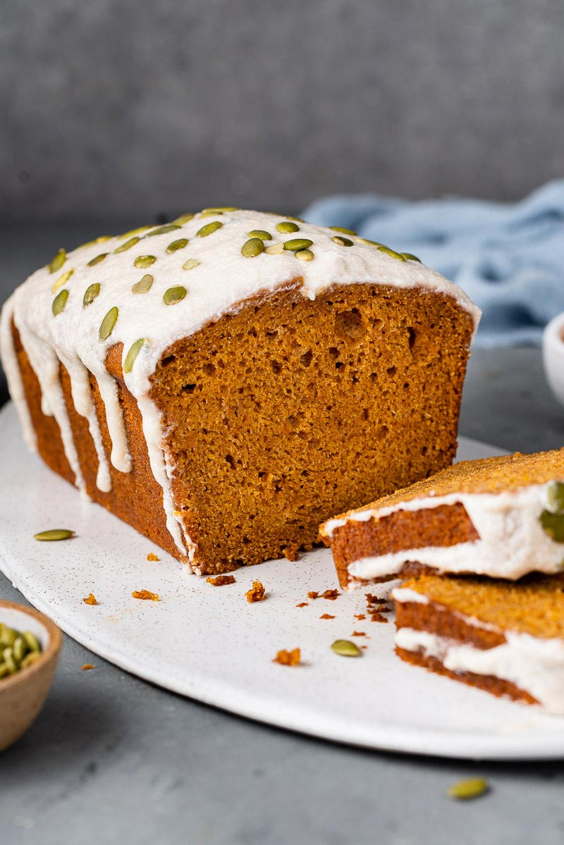 sliced vegan pumpkin bread with cream cheese icing and pumpkin seeds on white board