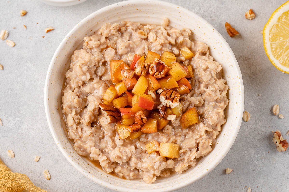 horizontal image of apple cinnamon oatmeal in bowl styled on a grey background